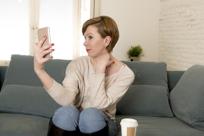 Young attractive and happy red hair woman sitting at home sofa couch drinking coffee taking selfie picture with mobile phone. Camera in internet social media stock images