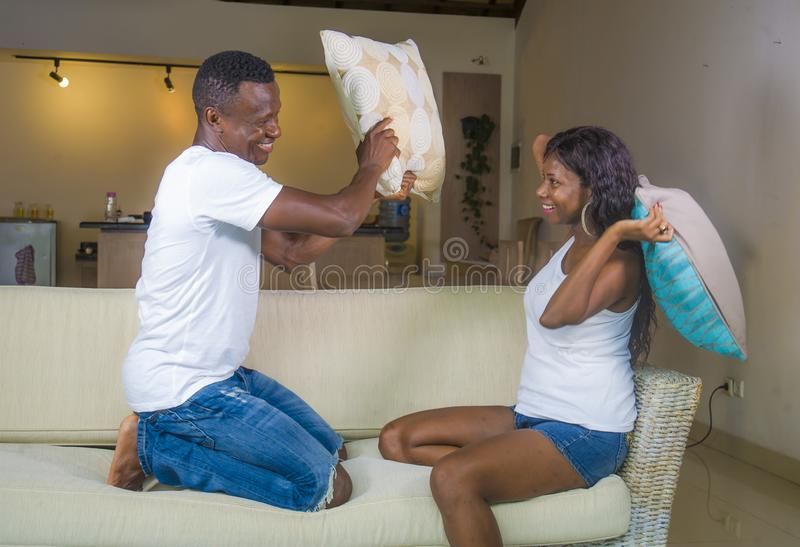 Young attractive and happy romantic African American couple in love playful at living room couch playing pillow fight enjoying stock photos