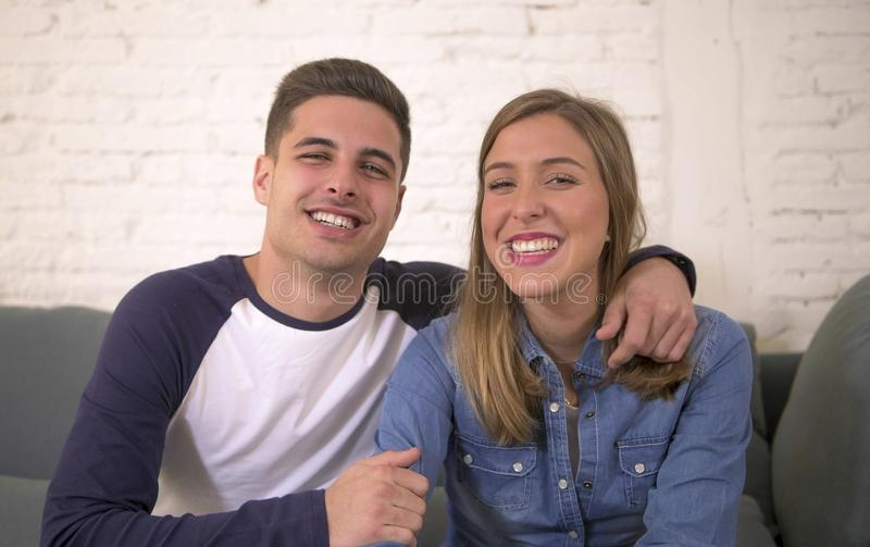 Young attractive happy and romantic couple boyfriend and girlfriend cuddle tender at home couch smiling playful in beautiful teena. Gers love and relationship royalty free stock photos