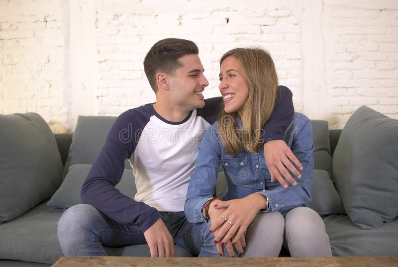 Young attractive happy and romantic couple boyfriend and girlfriend cuddle tender at home couch smiling playful in beautiful teena. Gers love and relationship stock photography