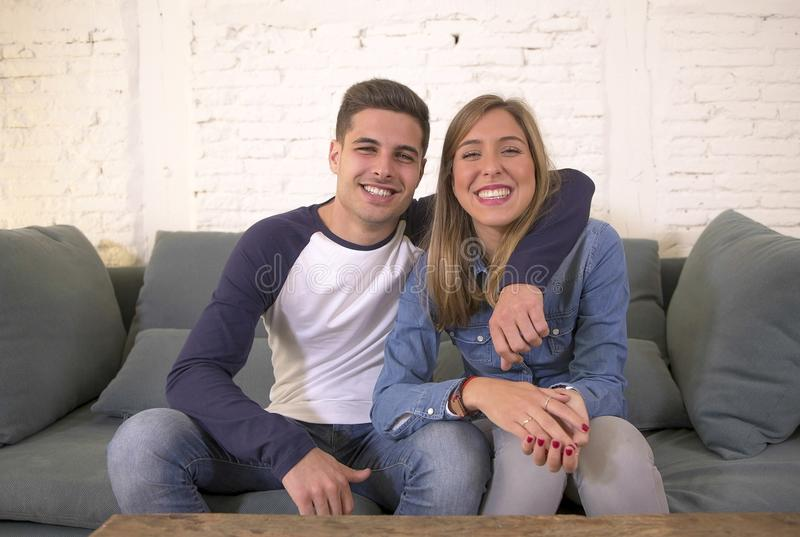 Young attractive happy and romantic couple boyfriend and girlfriend cuddle tender at home couch smiling playful in beautiful teena. Gers love and relationship stock image