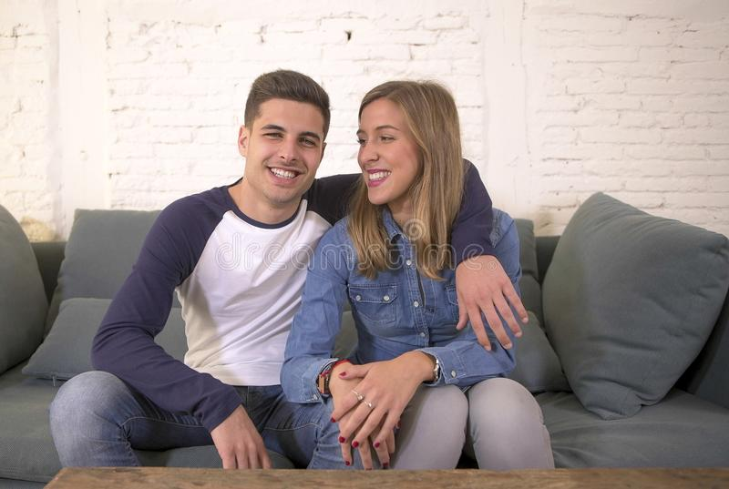 Young attractive happy and romantic couple boyfriend and girlfriend cuddle tender at home couch smiling playful in beautiful teena. Gers love and relationship stock photos