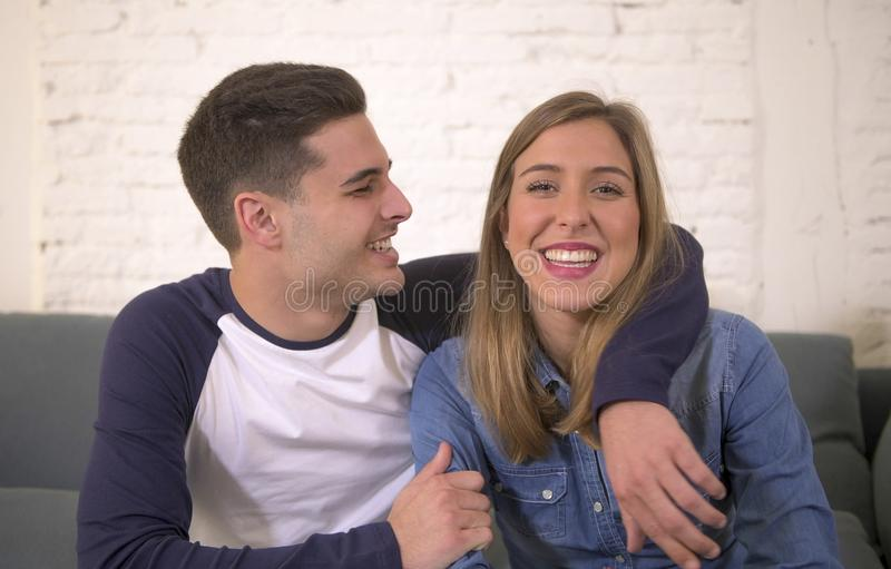 Young attractive happy and romantic couple boyfriend and girlfriend cuddle tender at home couch smiling playful in beautiful teena. Gers love and relationship royalty free stock images