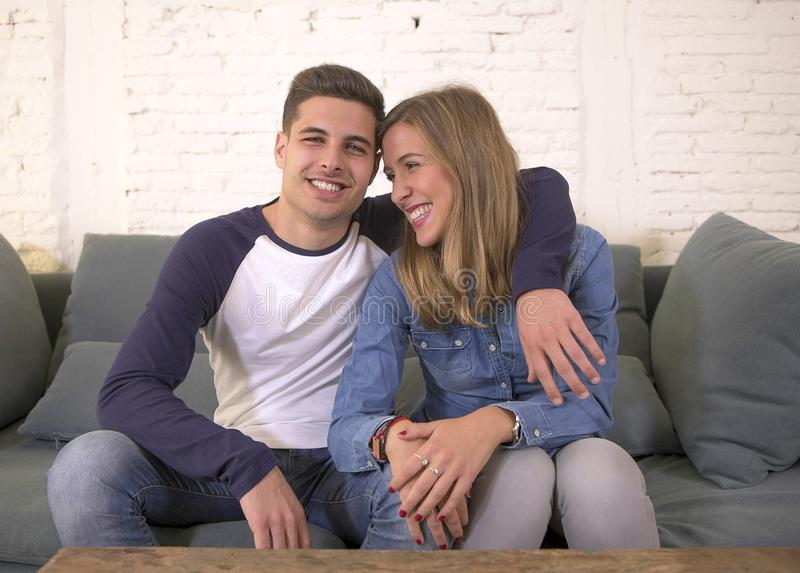 Young attractive happy and romantic couple boyfriend and girlfriend cuddle tender at home couch smiling playful in beautiful teena. Gers love and relationship royalty free stock photography