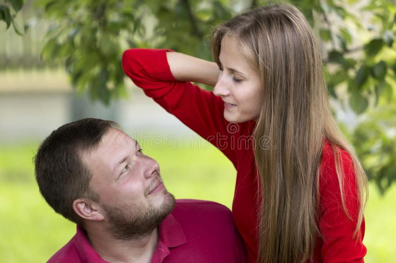 Young attractive happy romantic couple, pretty blond long-haired smiling girl and laughing unshaven man hugging together outdoors royalty free stock photography