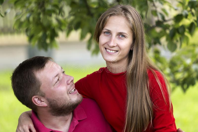 Young attractive happy romantic couple, pretty blond long-haired smiling girl and laughing unshaven man hugging together outdoors royalty free stock image
