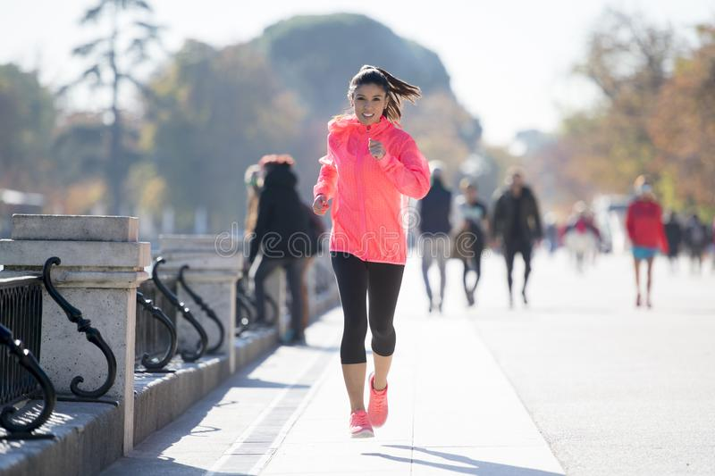 Happy runner woman in Autumn or Winter sportswear running and tr. Young attractive and happy runner woman in Autumn or Winter sportswear running and training on royalty free stock images