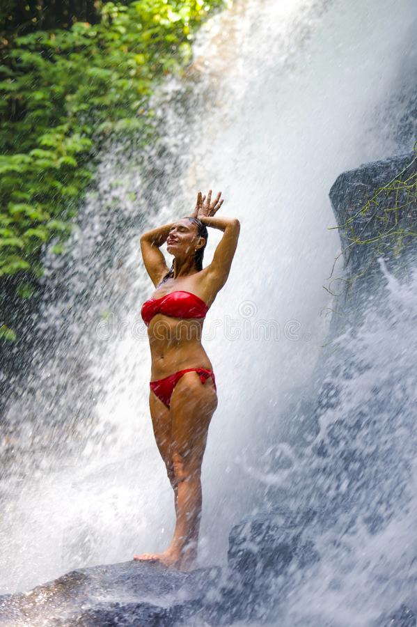 Young attractive and happy 30s woman with fit body practicing yoga wet under tropical paradise waterfall stream in meditation and. Young attractive and happy 30s stock photos