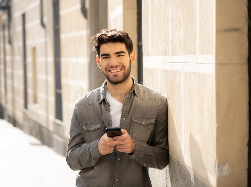 Young attractive happy stylish man on smart phone social network app in european city outdoors. Fashion college man in his twenties happy checking blog or royalty free stock image