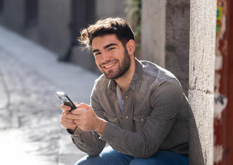 Young attractive happy stylish man on smart phone social network app in european city outdoors. Fashion college man in his twenties happy checking blog or royalty free stock images