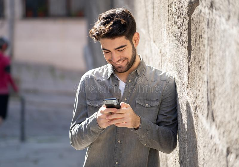 Young attractive happy stylish man on smart phone social network app in european city outdoors. Fashion college man in his twenties happy checking blog or stock photos