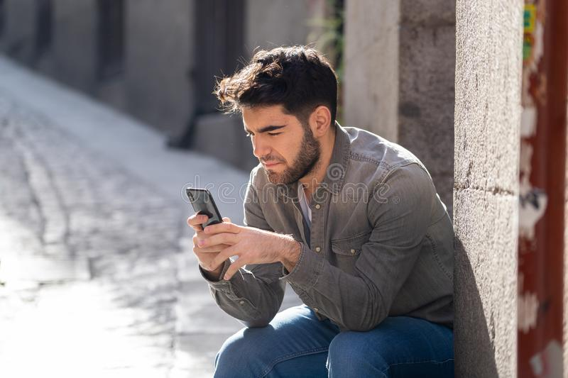 Young attractive happy stylish man on smart phone social network app in european city outdoors stock photo