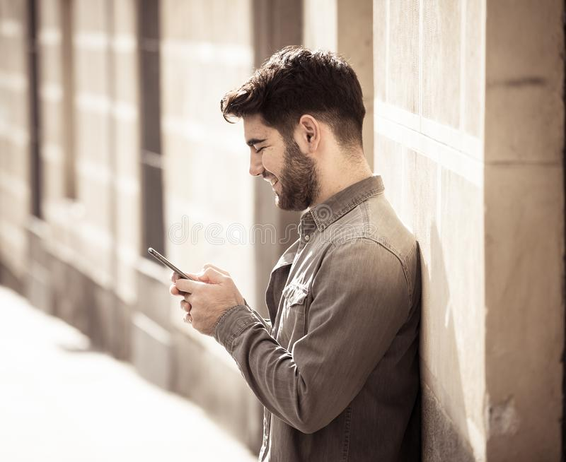 Young attractive happy stylish man on smart phone social network app in european city outdoors royalty free stock photos