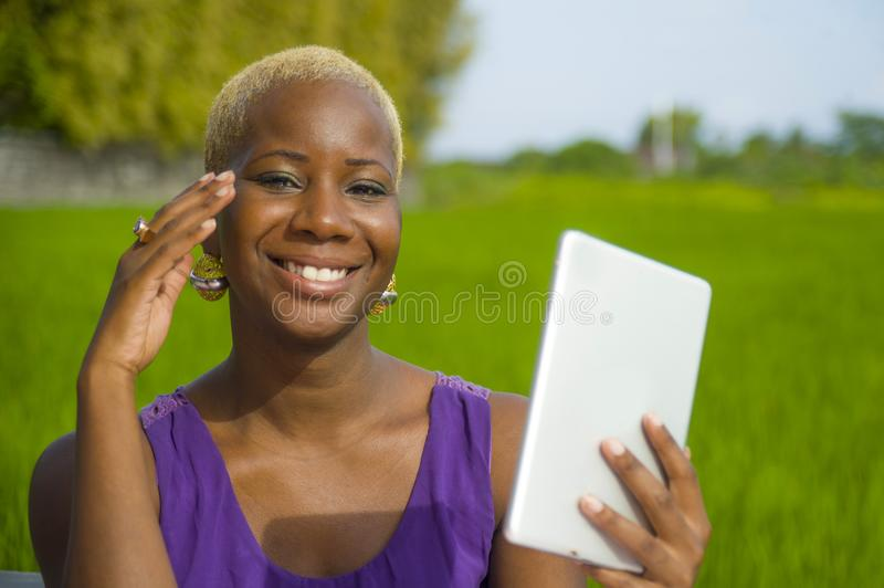 Young attractive and happy successful black afro american woman working with digital tablet pad outdoors on green field cafe smili. Young attractive and happy royalty free stock photo