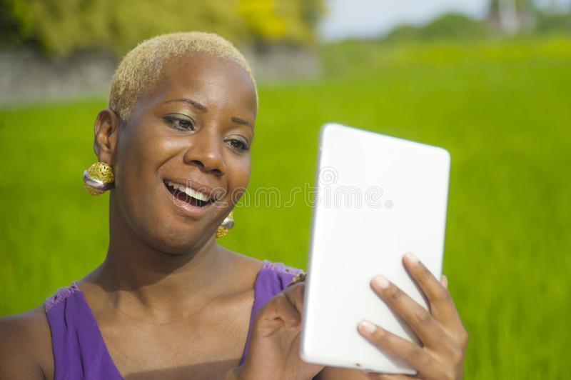 Young attractive and happy successful black afro american woman working with digital tablet pad outdoors on green field cafe smili. Young attractive and happy royalty free stock photography