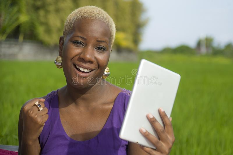 Young attractive and happy successful black afro american woman working with digital tablet pad outdoors on green field cafe smili. Young attractive and happy stock image