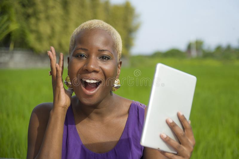 Young attractive and happy successful black afro american woman working with digital tablet pad outdoors on green field cafe smili. Young attractive and happy stock photography