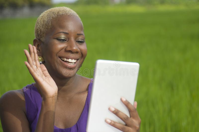 Young attractive and happy successful black afro american woman working with digital tablet pad outdoors on green field cafe smili. Young attractive and happy royalty free stock photos