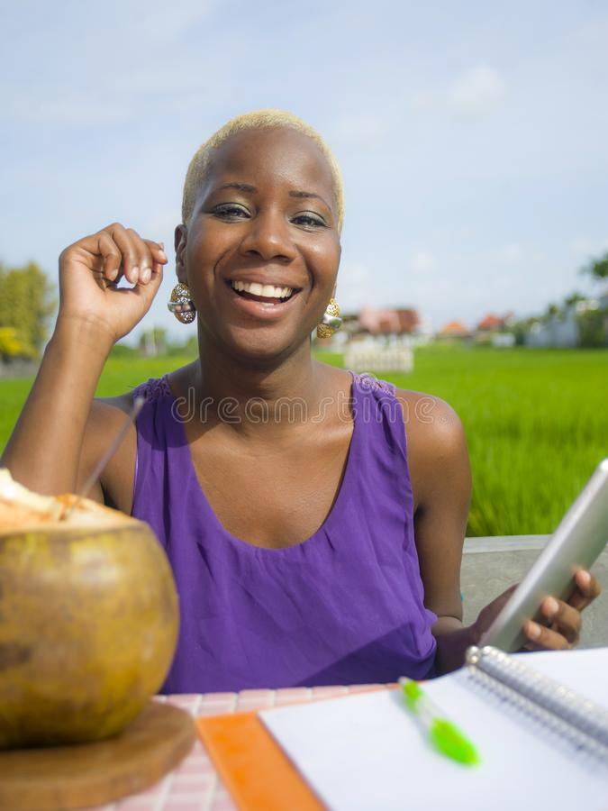Young attractive and happy successful black afro american woman working with digital tablet pad outdoors on green field cafe smili. Ng cheerful in digital nomad stock photo
