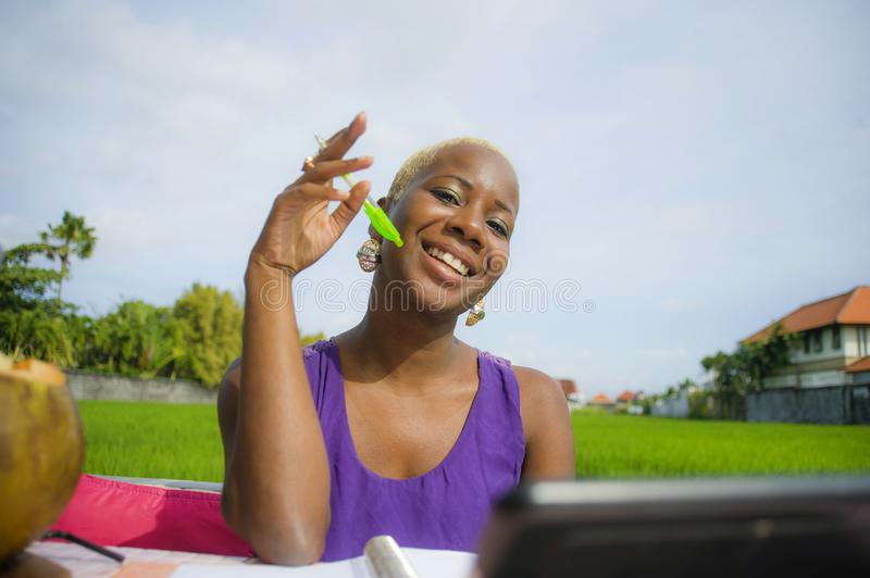 Young attractive and happy successful black afro american woman working with digital tablet pad outdoors on green field cafe smili. Ng cheerful in digital nomad stock image