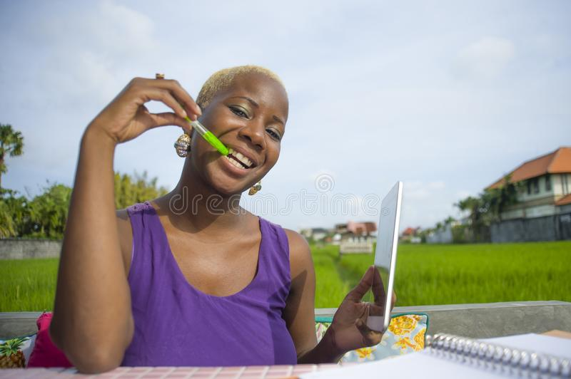 Young attractive and happy successful black afro american woman working with digital tablet pad outdoors on green field cafe smili. Ng cheerful in digital nomad royalty free stock photo