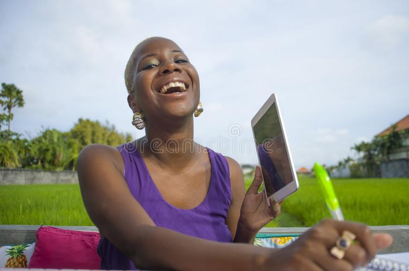 Young attractive and happy successful black afro american woman working with digital tablet pad outdoors on green field cafe smili. Ng cheerful in digital nomad royalty free stock images