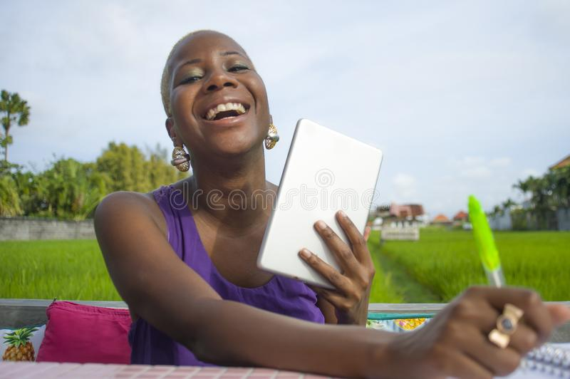 Young attractive and happy successful black afro american woman working with digital tablet pad outdoors on green field cafe smili. Ng cheerful in digital nomad royalty free stock image
