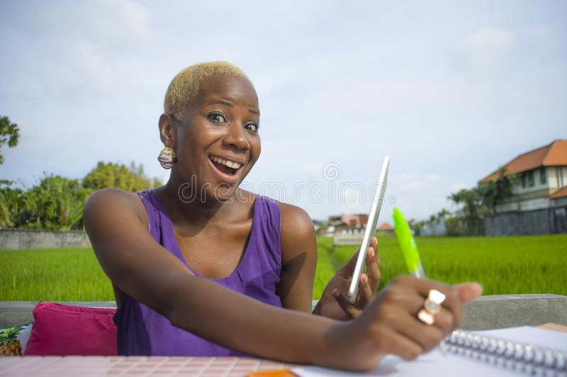Young attractive and happy successful black afro american woman working with digital tablet pad outdoors on green field cafe smili. Ng cheerful in digital nomad royalty free stock photography