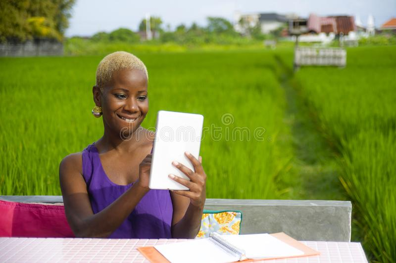 Young attractive and happy successful black afro american woman working with digital tablet pad outdoors on green field cafe smili. Ng cheerful in digital nomad stock photos