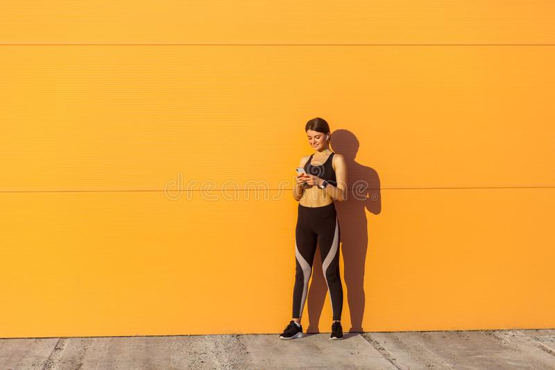 Young attractive happy woman wearing black sporwear standing near orange wall background, holding smartphone and writing message stock images