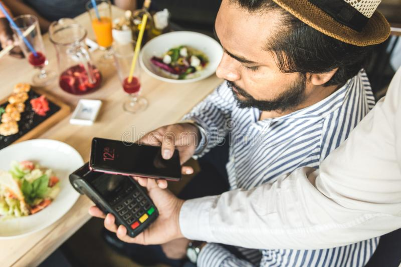 Young attractive Hindu man paying in cafe with contactless smartphone payment. Young attractive Hindu man making a contactless smartphone payment royalty free stock images
