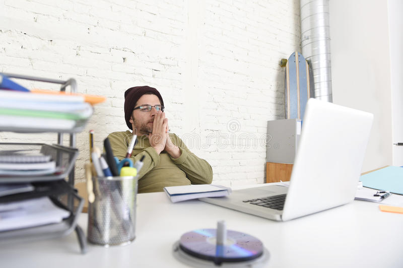 Young attractive hipster businessman working with computer in modern home office. Corporate portrait of young concentrated hipster businessman working with royalty free stock photos