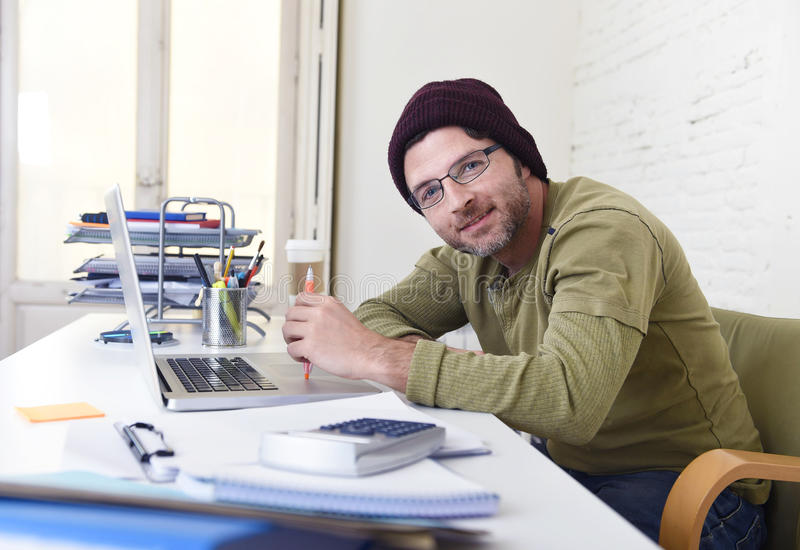 Young attractive hipster businessman working from his home office as freelancer self employed business model. Young happy hipster businessman working from his royalty free stock images
