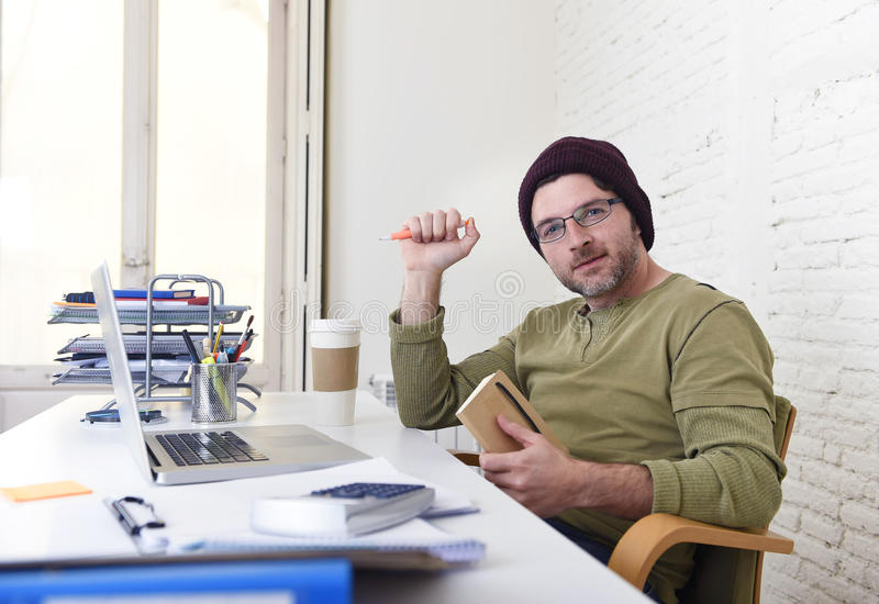Young attractive hipster businessman working from his home office as freelancer self employed business model. Young happy hipster businessman working from his stock photo