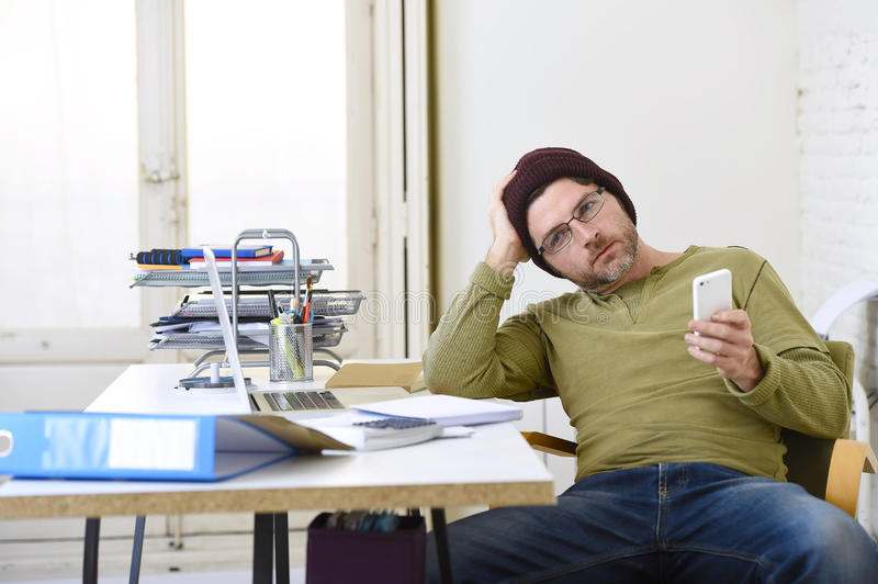 Young attractive hipster businessman working from his home office as freelancer self employed business model. Young attractive hipster businessman working from royalty free stock photos