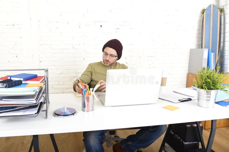Young attractive hipster businessman working from his home office as freelancer self employed business model. Young attractive hipster businessman working from royalty free stock image