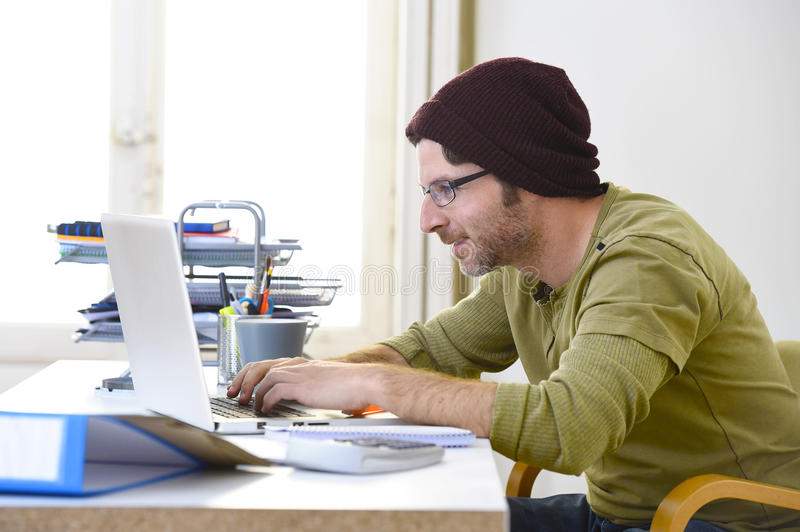Young attractive hipster businessman working from home office as freelancer self employed business model. Corporate portrait of young happy hipster businessman royalty free stock image