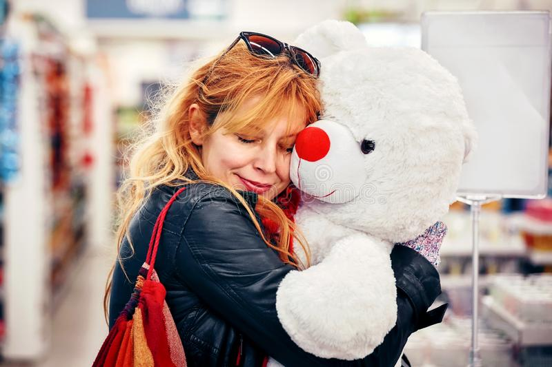 Young attractive hipster female smiling and hugging a big white teddy bear at the shop. Concept of valentine`s day stock photos