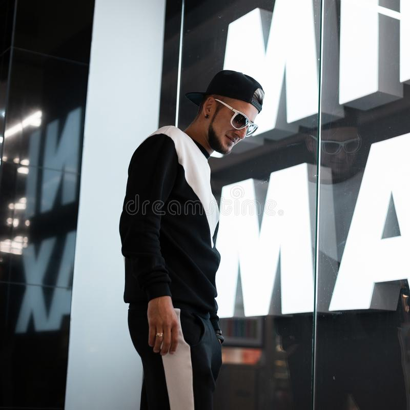 Young attractive hipster male with a beard in a black vintage cap in stylish sunglasses in a black fashionable sports suit walks. Through a shopping center royalty free stock photos