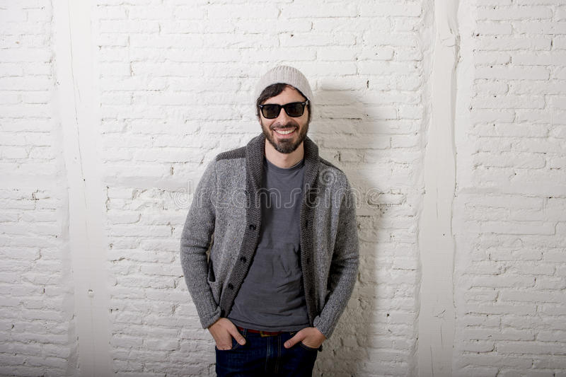 Young attractive hipster and trendy style looking man posing cool with attitude dressing informal. Young attractive hipster and trendy style looking man smiling stock images