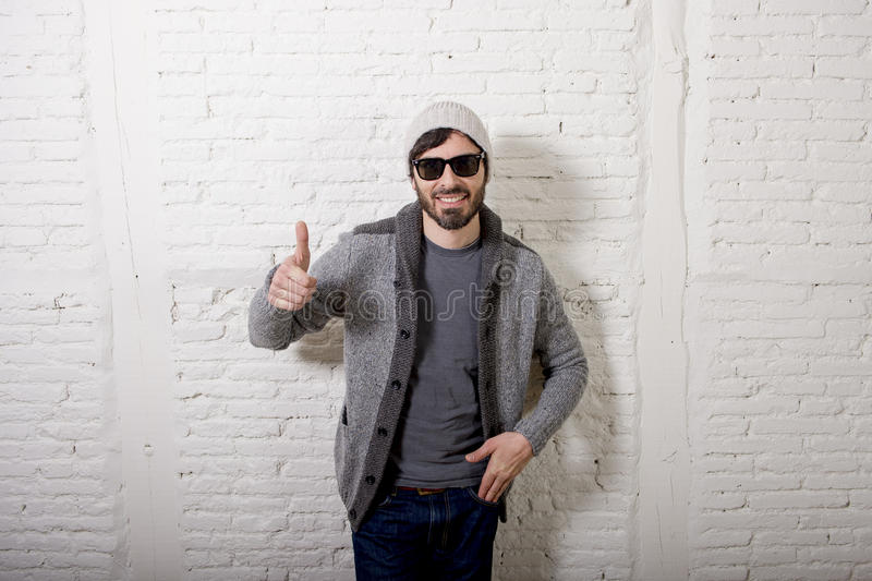 Young attractive hipster and trendy style looking man posing cool with attitude dressing informal. Young attractive hipster and trendy style looking man smiling royalty free stock image