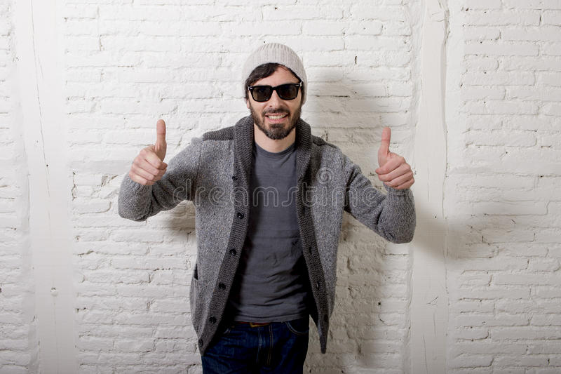 Young attractive hipster and trendy style looking man posing cool with attitude dressing informal. Young attractive hipster and trendy style looking man smiling stock photography