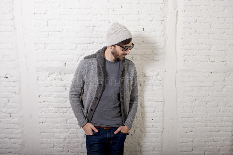 Young attractive hipster and trendy style looking man posing cool with attitude dressing informal. Wearing casual beanie beard and sunglasses in male fashion stock photo