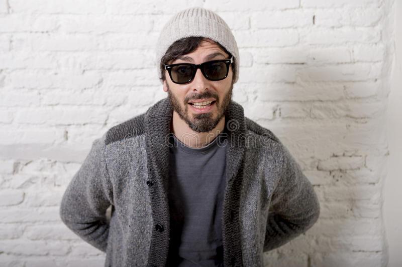 Young attractive hipster and trendy style looking man posing cool with attitude dressing informal. Wearing casual beanie beard and sunglasses in male fashion royalty free stock photo