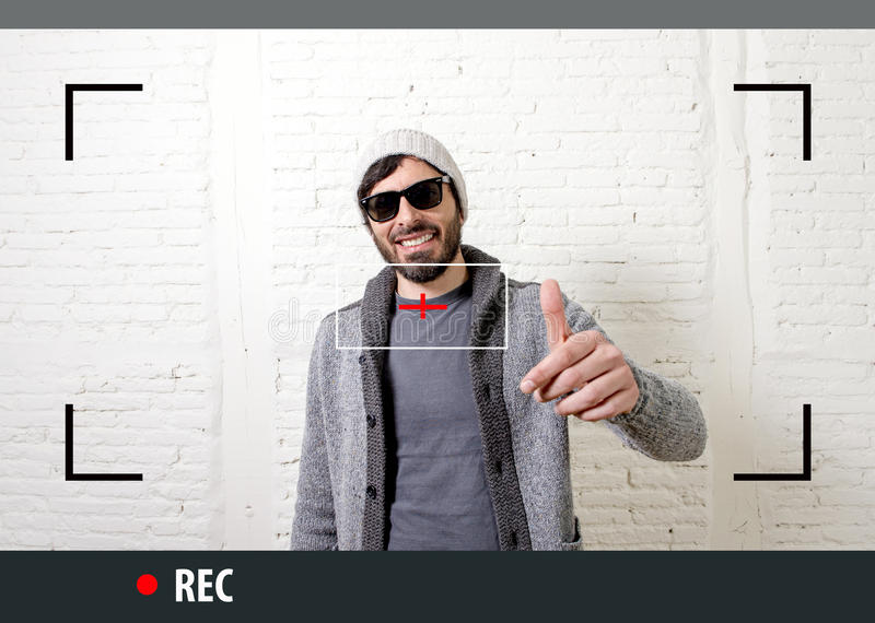 Young attractive hipster and trendy style man in selfie and internet video blogger recording. Young attractive vlog hipster and trendy style looking man smiling royalty free stock photo