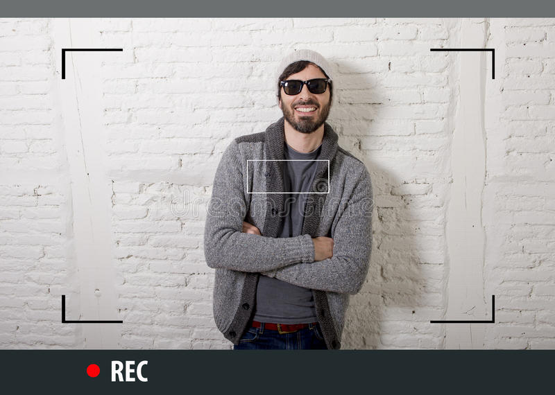 Young attractive hipster and trendy style man in selfie and internet video blogger recording. Young attractive vlog hipster and trendy style looking man smiling royalty free stock photography