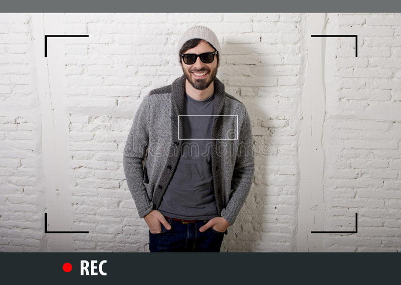 Young attractive hipster and trendy style man in selfie and internet video blogger recording. Young attractive vlog hipster and trendy style looking man smiling royalty free stock images