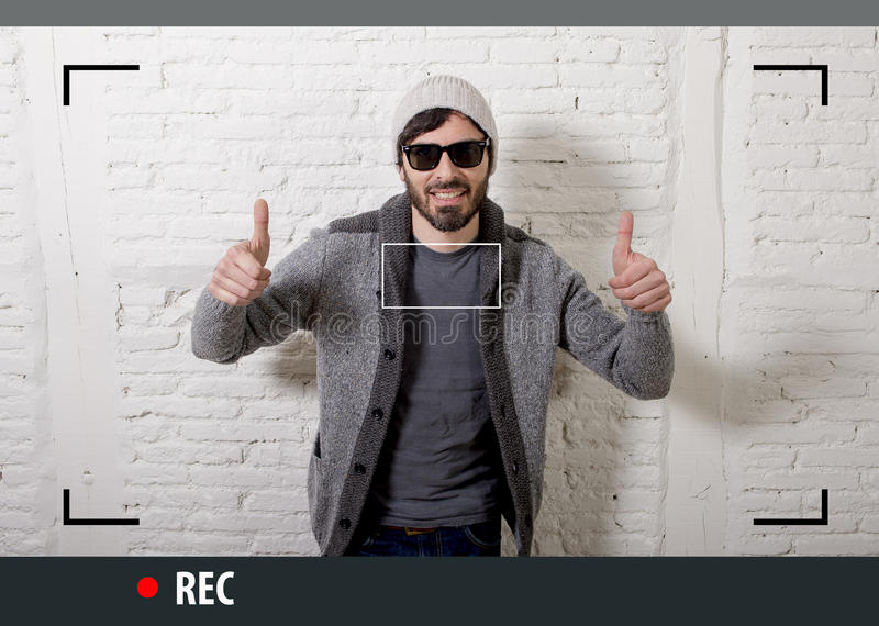 Young attractive hipster and trendy style man in selfie and internet video blogger recording stock photos
