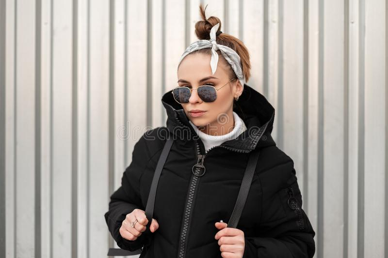 Young attractive hipster woman with stylish hairstyle with a bandana in black glasses in a long black coat with a backpack. On her shoulders posing near a metal royalty free stock photo