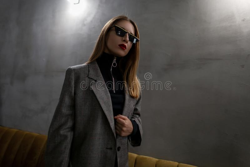 Young attractive hipster woman in unusual stylish glasses in a vintage elegant checkered jacket in a black stylish shirt stock image